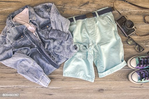 917262406istockphoto Men clothing - shoes, jeans and shirt on white wooden background 805460282