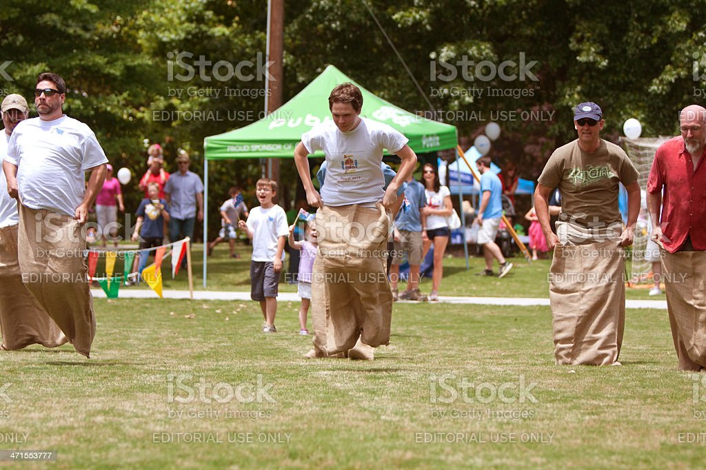 Men Compete In Sack Race At Spring Festival stock photo