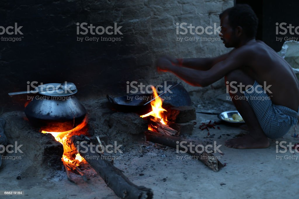 Men cooking food on mud stove outdoor stock photo