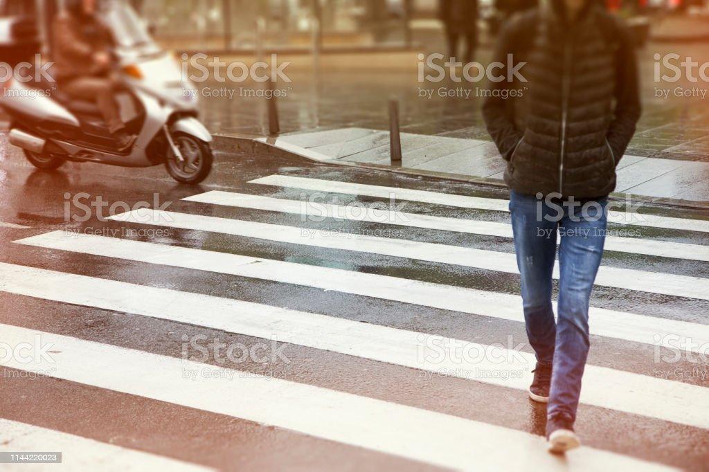 Men crossing the street in rainy day