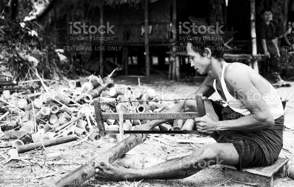 Men cutting bamboo outside his house, Myanmar stock photo