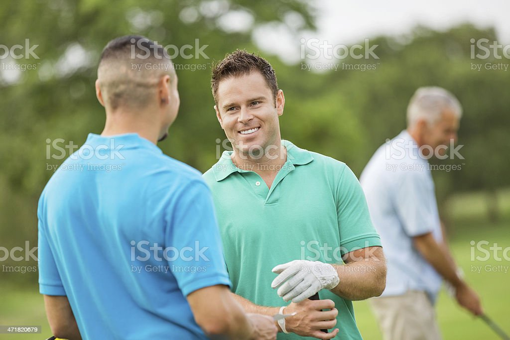 Men discussing business on the golf course while teeing off royalty-free stock photo
