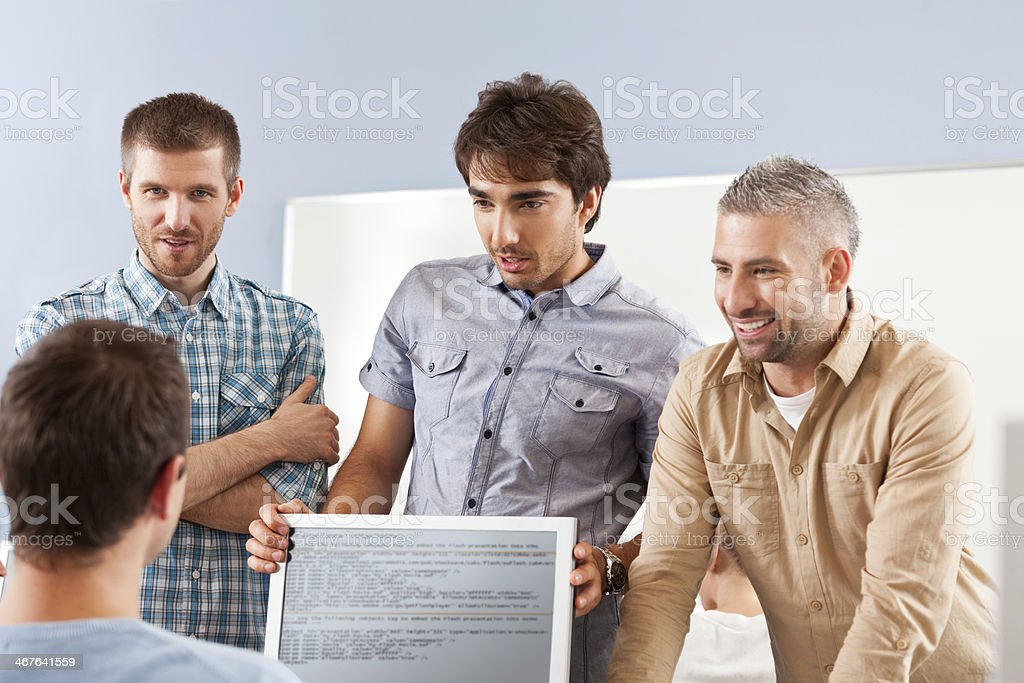 Men discussing project Four mid adult men discussing project together.  30-39 Years Stock Photo