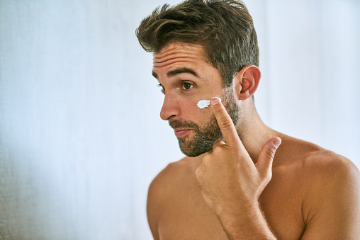 Shot of a handsome young man applying moisturizer at home