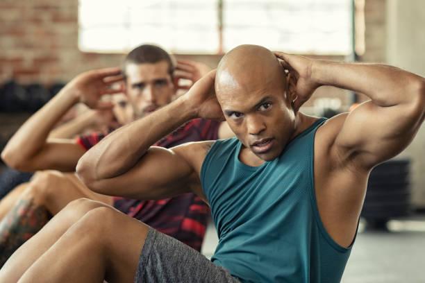 men doing sit ups workout - class стоковые фото и изображения