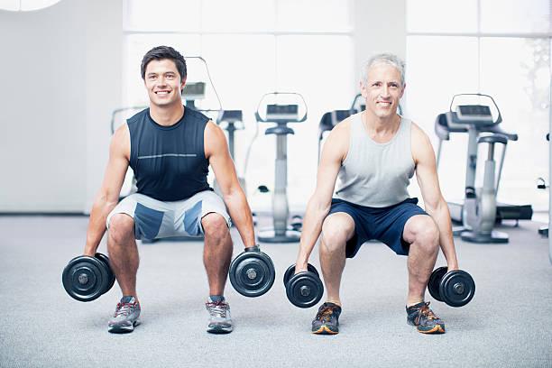Hombre haciendo squats con pesas en el gimnasio - foto de stock