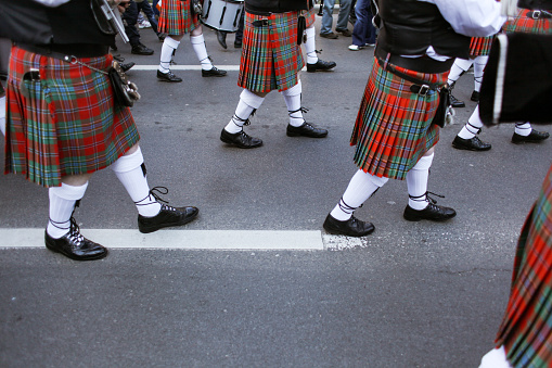 Men dressed in Irish traditional kilts march on the streets during St Patrick's Day.