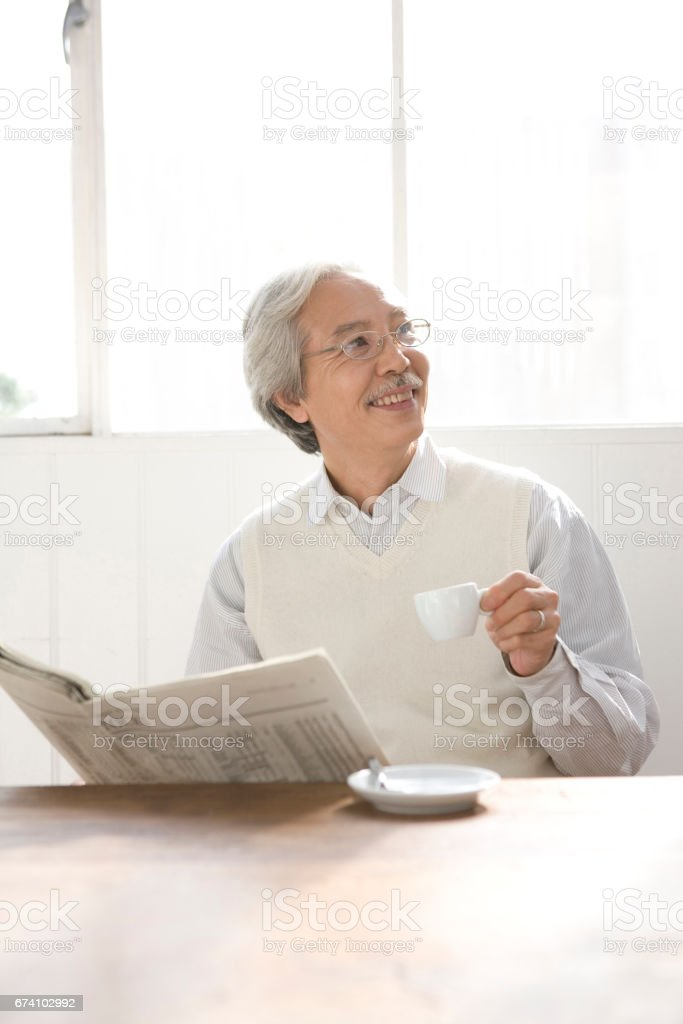 Men drink coffee while reading the newspaper royalty-free stock photo