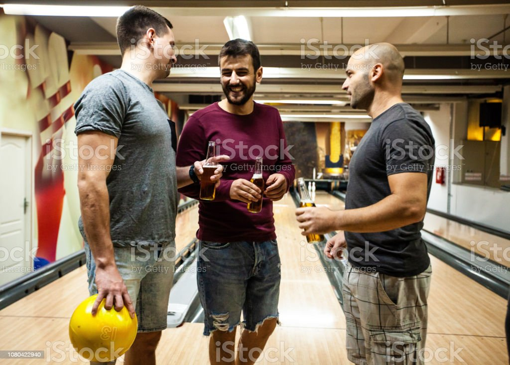 Men drinking beer in bowling alley stock photo