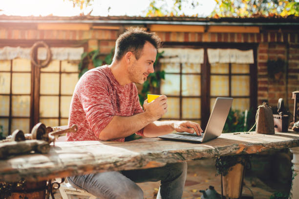 Men drinking coffee and using laptop at backyard patio stock photo