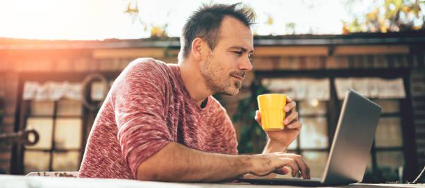 männer trinken kaffee und mit laptop im hinterhof patio - letzter arbeitstag stock-fotos und bilder