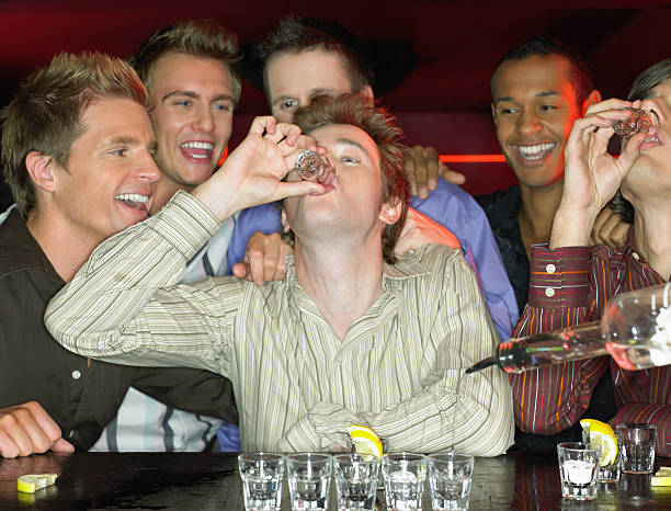 Men drinking shots at a bar stock photo
