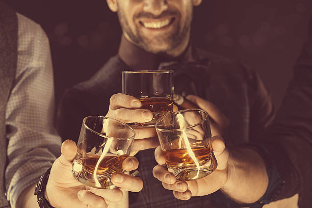 men drinking whiskey, close up of glasses and hands - whiskey stock photos and pictures