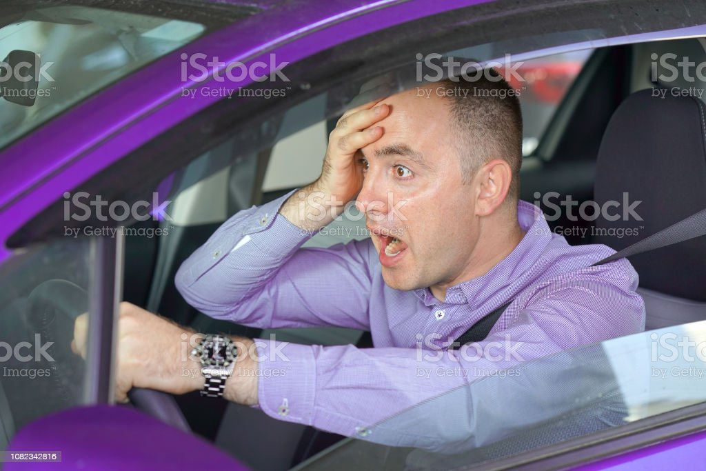 Side window view of inexperienced anxious motorist. Man driving a...