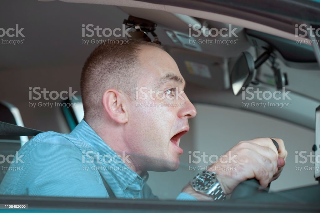 Side window view of inexperienced anxious motorist. Young man driving...