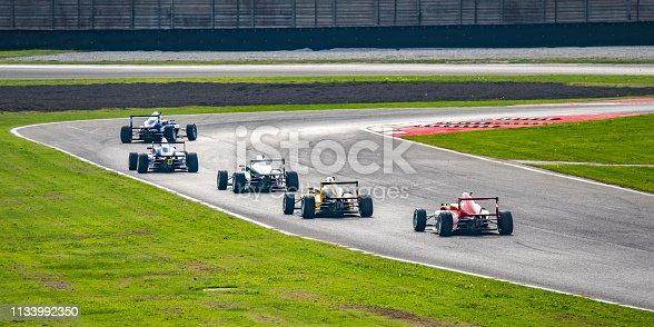 Men driving formula racing cars on motor racing track.