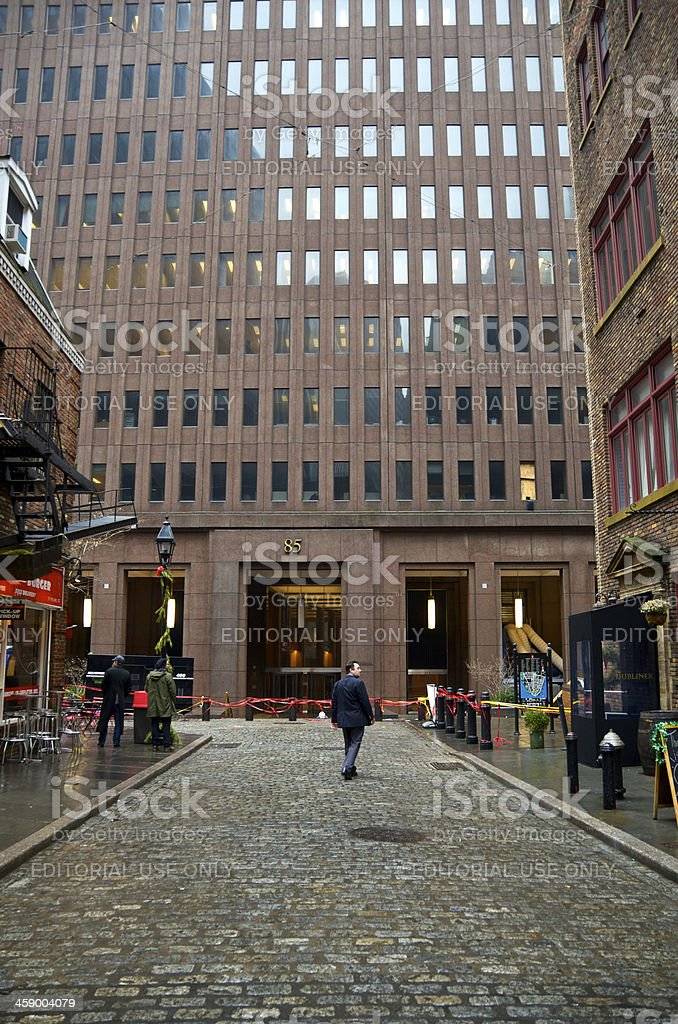 Men dwarfed by office building, Manhattan Financial District, NYC royalty-free stock photo