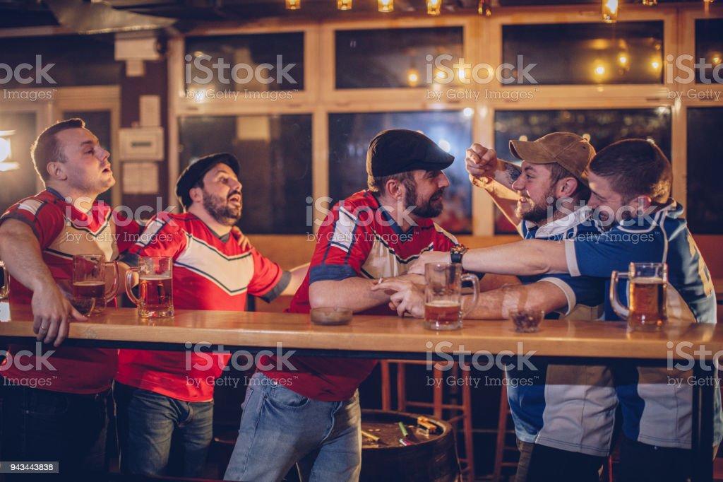 Men fighting in sports bar stock photo