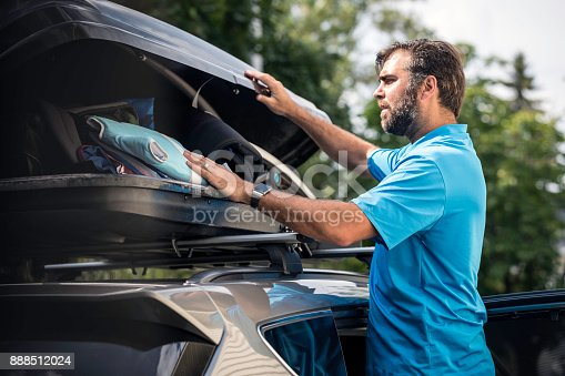 istock Men Filling Cargo Box Container on Roof Rack for Vacations 888512024