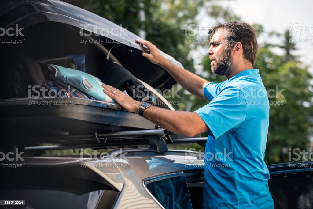 Men Filling Cargo Box Container on Roof Rack for Vacations stock photo