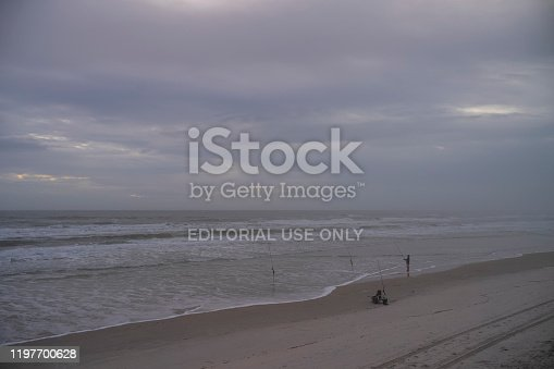1054156720istockphoto Men fish with fishing rods off the Atlantic coast during a morning sunrise at Wilber-By-The-Sea, Florida. 1197700628