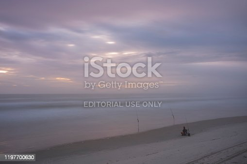 1054156720istockphoto Men fish with fishing rods off the Atlantic coast during a morning sunrise at Wilber-By-The-Sea, Florida. 1197700630