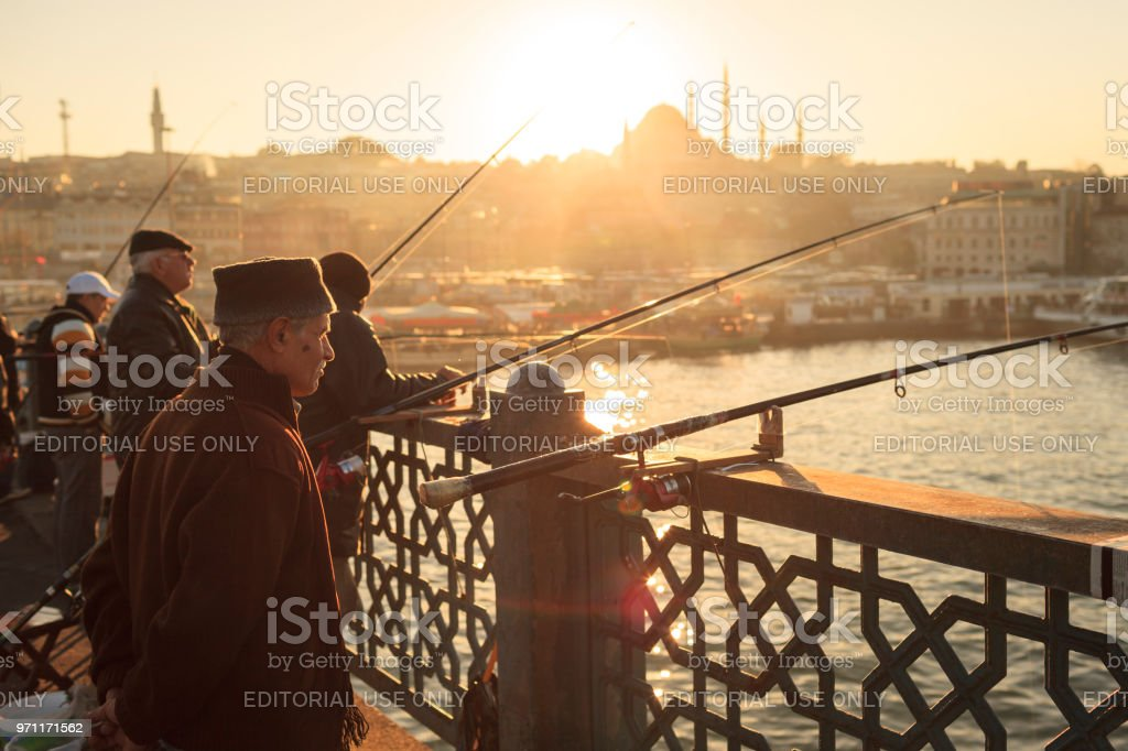 Men fishing at sunset on the Galata Bridge, Istanbul, Turkey stock photo
