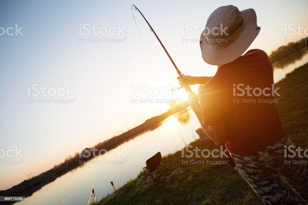 Men fishing in sunset and relaxing while enjoying hobby stock photo