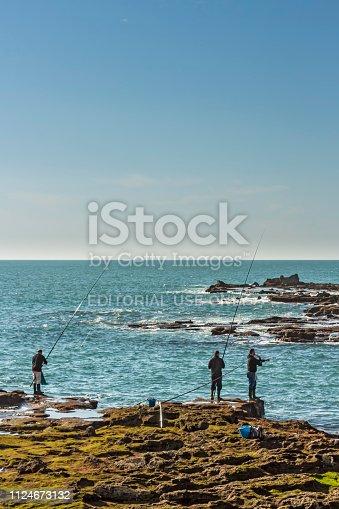 istock Men fishing off the rocks of Paseo Fernando Quinones in Cadiz 1124673132
