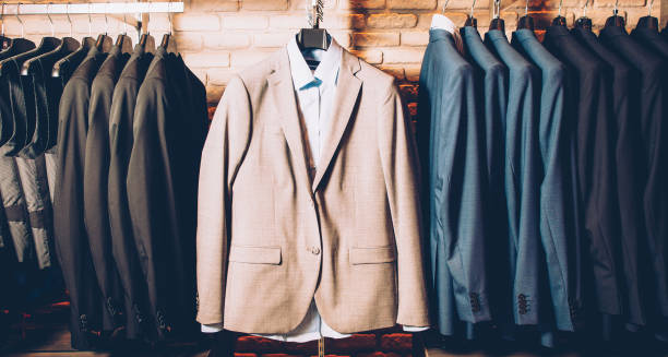 men formal wear classy outfit business suit Men formal wear. Classy outfit. Modern clothing store. Business suit jackets and vests hanging, displayed over brick wall. mens fashion stock pictures, royalty-free photos & images