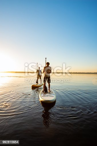 Men, friends relax on a SUP boards in large river during sunset. Stand up paddle boarding - awesome active recreation in nature. Backlight, wide angle.