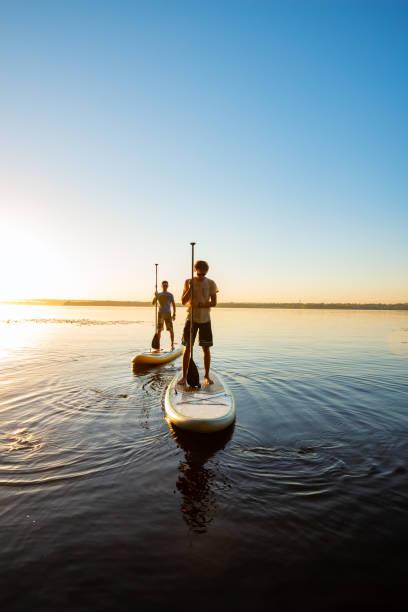 männer, freunde auf ein sup-boards bei sonnenuntergang entspannen - stehpaddeln stock-fotos und bilder