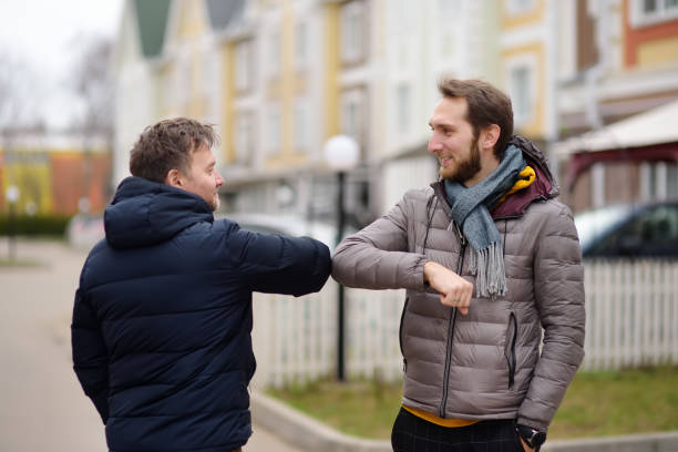 Men greeting each other with elbows instead of handshake. Friends or colleagues touch elbows . Alternative non-contact greeting during coronavirus epidemic. Safety while COVID-19. stock photo
