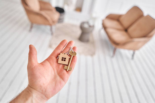 Men hand holding key with house shaped keychain. Modern light lobby interior. Mortgage concept. Real estate, moving home or renting property. stock photo