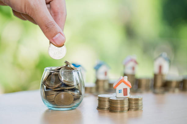 eine männer hand stapeln goldmünzen und hausmodell, geld zu sparen für ein neues zuhause und investitionen mit immobilien-konzept zu kaufen. - spenden sammeln stock-fotos und bilder
