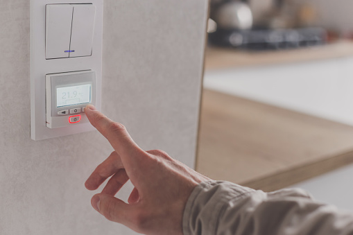 istock Men hand setting the temperature on control panel of DHW or central heating. 1219707930