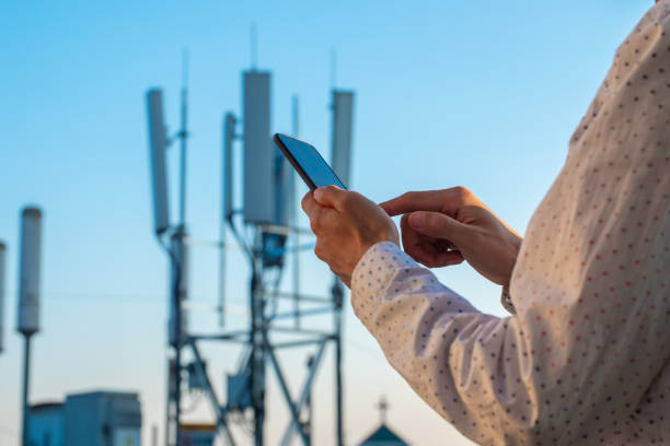 Men hand using phone with 5G telecommunications station tower background stock photo