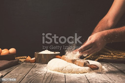 istock Men hands sprinkle a dough with flour close up 692778408