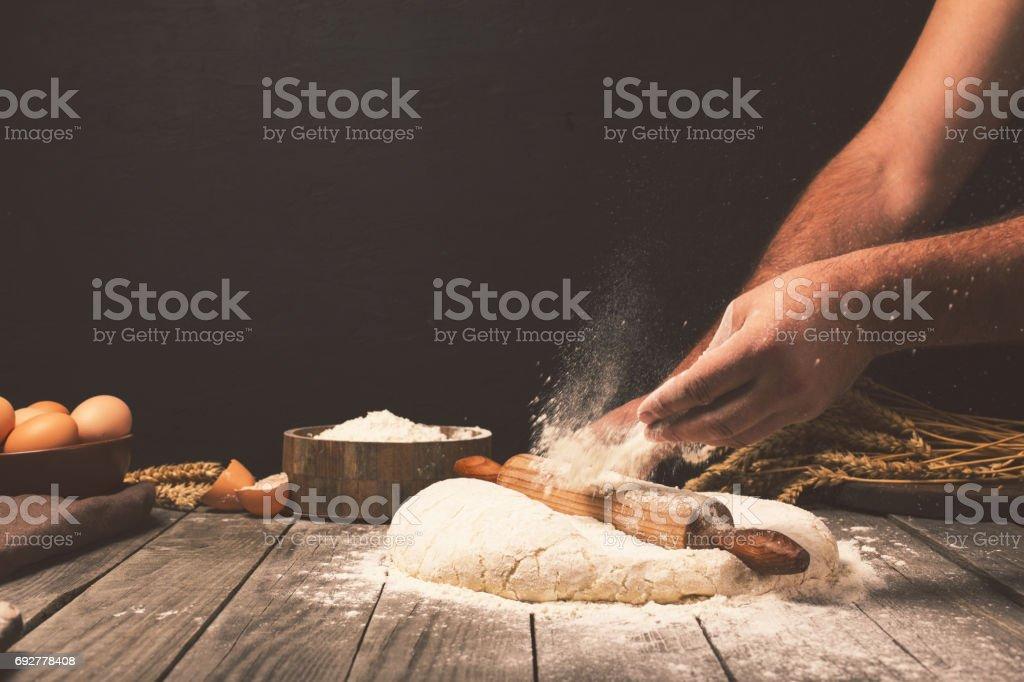 Men hands sprinkle a dough with flour close up stock photo