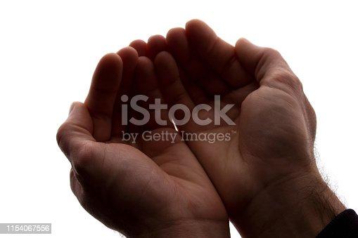 istock Men hands together, handful - silhouette 1154067556