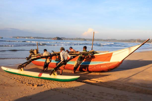 Männer, die ein traditionelles Fischerboot an Land schleppen – Foto