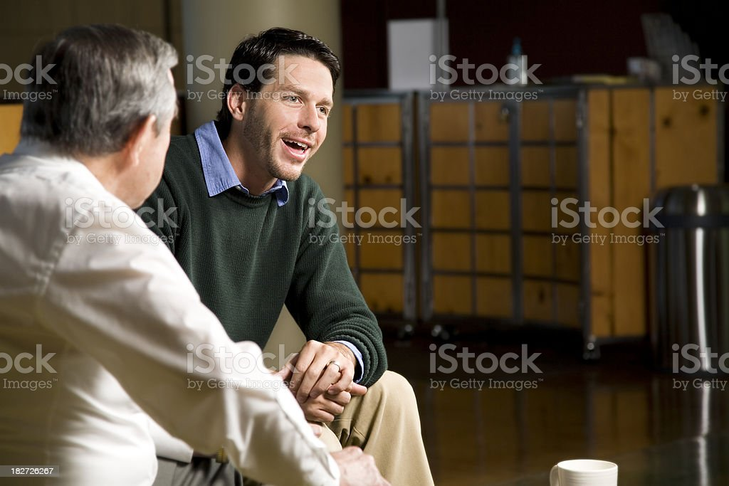 Men Having a Friendly Discussion Indoors royalty-free stock photo