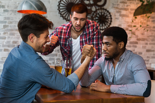 Men Having Fun Arm Wrestling Each Other In Bar Stock Photo - Download Image Now - iStock