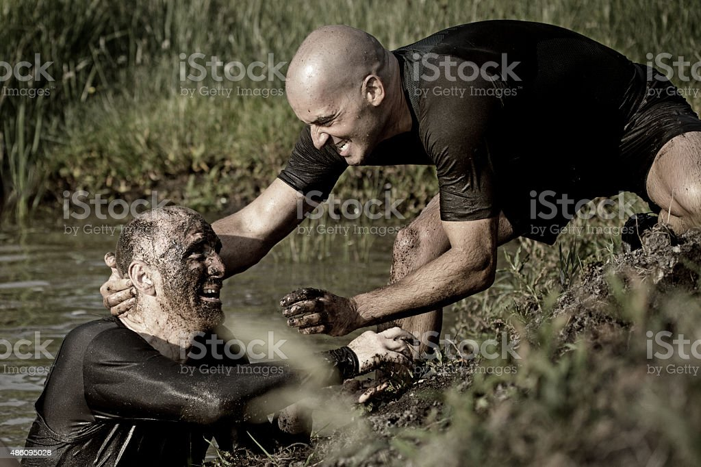 men having fun during mud run stock photo
