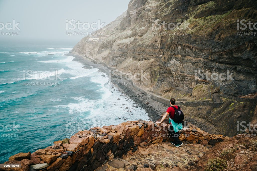 Men hiker with backpack on the scenic coastal road. The route leads along huge volcanic rock cliffs above roaring ocean and joins the towns of Cruzinha and Ponta do Sol. Santo Antao. Cape Verde stock photo