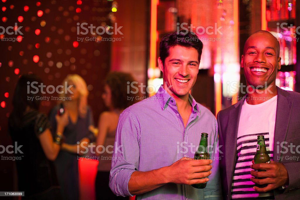 Men holding beer bottles in nightclub stock photo