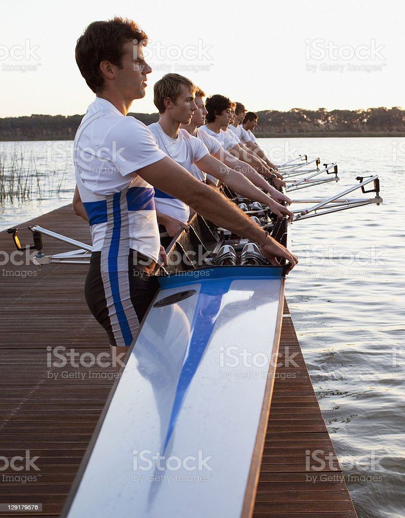Men holding canoe on pier royalty-free stock photo