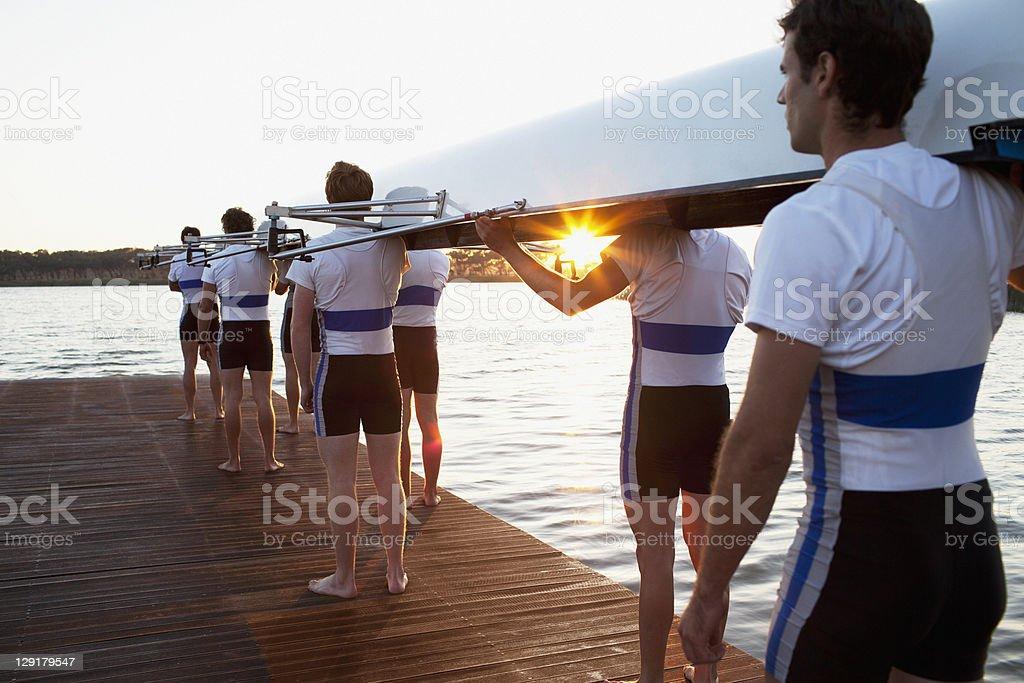 Men holding canoe on shoulders royalty-free stock photo