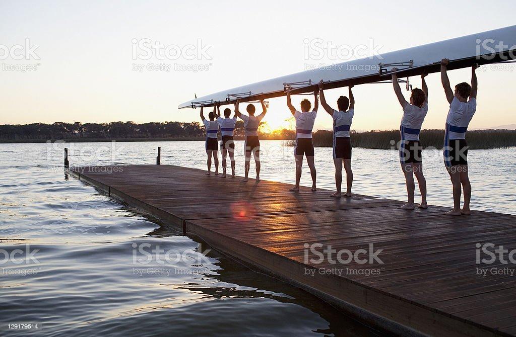Homens segurando canoa mais de chefes - foto de acervo