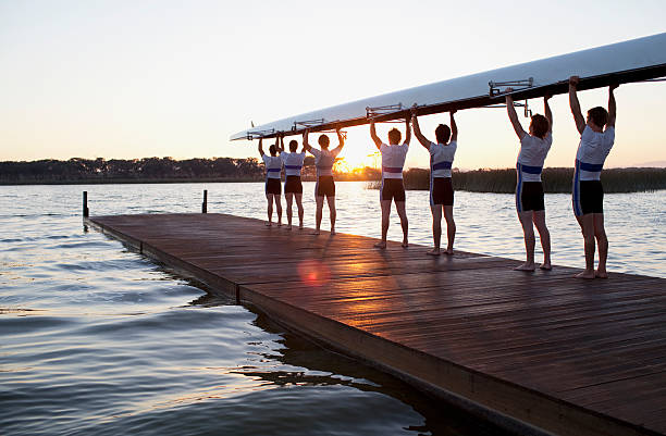 men holding canoe over heads - sports team stock photos and pictures